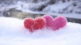 Corações de lã vermelhos e cor-de-rosa na neve branca na costa do rio no inverno vídeos de arquivo