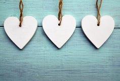 Corações de madeira brancos decorativos em um fundo de madeira rústico azul com espaço da cópia Foco seletivo imagem de stock
