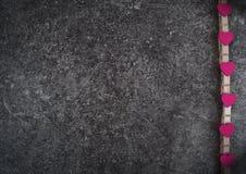 Corações de madeira cor-de-rosa pequenos no fundo cinzento do grunge Imagens de Stock Royalty Free