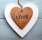 Corações de madeira decorativos em um fundo de madeira azul Dois corações do Valentim Conceito do dia ou do amor do ` s do Valent Fotografia de Stock