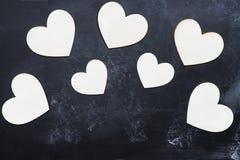 Corações de madeira do dia do ` s do Valentim do entalhe sobre o quadro-negro Imagens de Stock