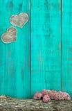 Corações de madeira que penduram na cerca azul da cerceta antiga com beira do log e das flores Imagens de Stock Royalty Free