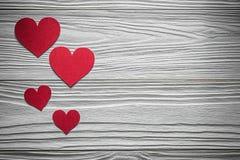 Corações de papel vermelhos em cartões do Valentim da placa de madeira Fotos de Stock