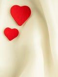 Corações decorativos de madeira vermelhos no fundo de seda branco. Foto de Stock Royalty Free