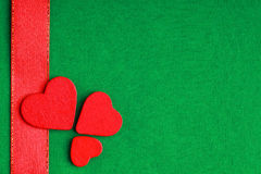 Corações decorativos de madeira vermelhos no fundo verde de pano Fotografia de Stock