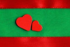 Corações decorativos de madeira vermelhos no fundo verde de pano Fotos de Stock Royalty Free