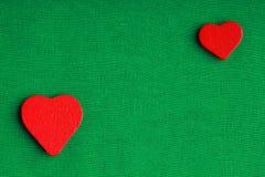 Corações decorativos de madeira vermelhos no fundo verde de pano Fotografia de Stock Royalty Free