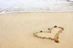 Corações desenhados na areia com seafoam e onda Foto de Stock