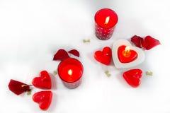Corações do dia de Valentim, velas e pétalas cor-de-rosa no backgro branco Foto de Stock
