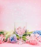 Corações do flor dos jacintos e os de vidro no copo de vinho sobre a luz - fundo cor-de-rosa Imagens de Stock Royalty Free