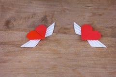 Corações do origâmi com asas em um fundo de madeira Dois corações fotografia de stock
