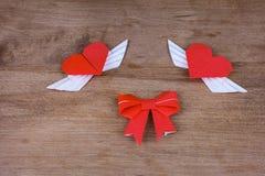 Corações do origâmi com asas em um fundo de madeira Dois corações Imagens de Stock Royalty Free