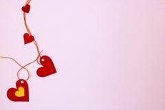 Corações do papel - conectado verticalmente, em um fundo cor-de-rosa delicado Fotografia de Stock