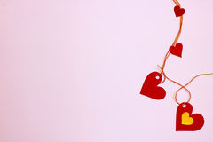 Corações do papel - conectado verticalmente, em um fundo cor-de-rosa delicado Foto de Stock