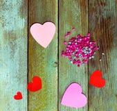 Corações e bolas de papel vermelhos e cor-de-rosa em placas de madeira velhas do grunge, vista superior Imagem de Stock