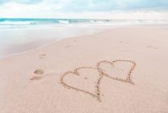 Corações e pegadas na praia Fotos de Stock