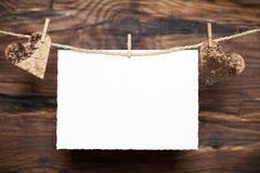 Corações e um cartão na frente do fundo de madeira Imagem de Stock Royalty Free