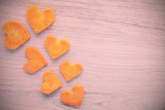 Corações estilizados retros feitos da cenoura no fundo do grunge Imagem de Stock