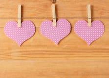 Corações feitos a mão que penduram na linha contra a parede da madeira-grão Fotografia de Stock