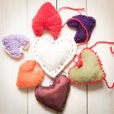 Corações feitos malha coloridos na luz, placas de madeira Foto de Stock