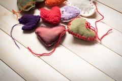 Corações feitos malha coloridos na luz, placas de madeira Imagens de Stock
