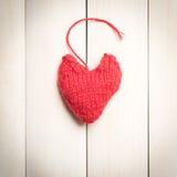 Corações feitos malha coloridos na luz, placas de madeira Fotografia de Stock Royalty Free