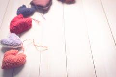 Corações feitos malha coloridos na luz, placas de madeira Imagem de Stock Royalty Free