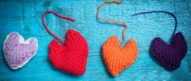 Corações feitos malha coloridos nas placas azuis Foto de Stock