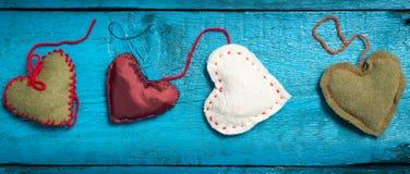 Corações feitos malha coloridos nas placas azuis Foto de Stock Royalty Free