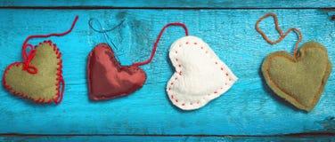 Corações feitos malha coloridos nas placas azuis Imagem de Stock Royalty Free