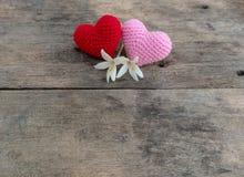 Cora??es nitting vermelhos e cor-de-rosa com as flores na tabela de madeira imagens de stock