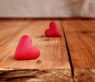 Corações pequenos em um fundo de madeira Imagens de Stock