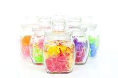 Corações plásticos coloridos nos frascos de vidro. Foto de Stock