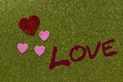 Corações sparkly vermelhos e cor-de-rosa no fundo verde que diz o amor, Fotos de Stock Royalty Free