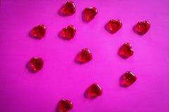 Corações vermelhos claros no fundo cor-de-rosa para o dia de Valentim imagens de stock