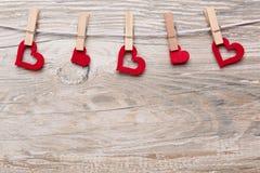 Corações vermelhos com pregadores de roupa em uma trela pendurada Imagem de Stock Royalty Free