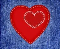 Corações vermelhos de matéria têxtil em calças de brim da tela no estilo do grunge Foto de Stock Royalty Free
