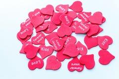 Corações vermelhos dispersados como o símbolo do casamento branco do fundo do amor fotos de stock royalty free