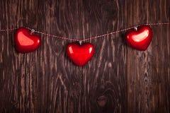 Corações vermelhos do brinquedo que penduram a fita no fundo de madeira, Imagens de Stock