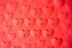 Corações vermelhos do fundo cortados do papel em um fundo vermelho Palavras EU TE AMO fotos de stock royalty free