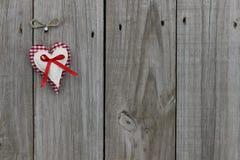 Corações vermelhos do guingão e da musselina que penduram na porta de madeira Fotografia de Stock Royalty Free
