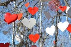 Corações vermelhos e corações brancos contra o céu azul e as árvores Imagens de Stock