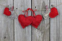 Corações vermelhos e de madeira do país que penduram na corda com fundo de madeira Foto de Stock Royalty Free