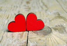 Corações vermelhos em um fundo de madeira Símbolo dos corações do amor Foto de Stock