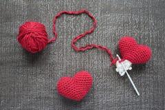 Corações vermelhos feitos crochê em uma placa do grunge Imagens de Stock