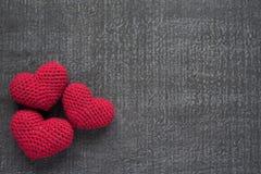 Corações vermelhos feitos crochê em uma placa do grunge Fotos de Stock