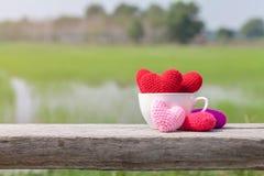 Corações vermelhos no copo cerâmico branco na madeira Fotografia de Stock
