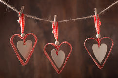 Corações vermelhos que penduram sobre o fundo de madeira imagens de stock royalty free