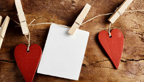 Corações vermelhos rústicos e nota vazia em uma corda Foto de Stock