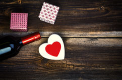 Corações, vinho e presentes na placa de madeira Imagens de Stock